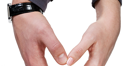 Female and male hands making love heart over white background